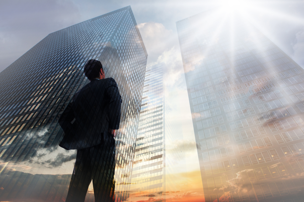 Businessman standing with hands on hips against low angle view of skyscrapers at sunset