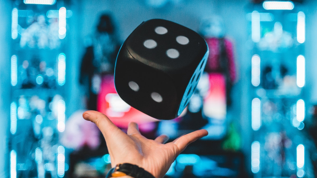 a hand throwing a big die into the air in a flashy-looking arcade